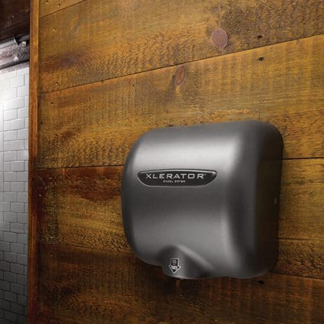 Graphite Textured Painted Excel XLERATOR hand dryer against rustic wood.