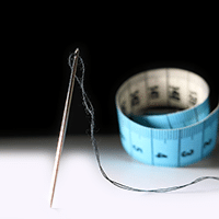 Photograph of needle, thread, and measuring tape used by tailor.