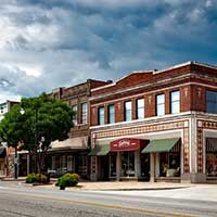 Photograph of small town shops in Alabama, storm clouds above.