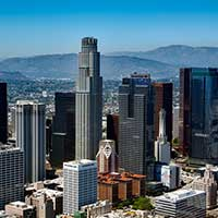 Aerial photograph of downtown Los Angeles skyscrapers, mountains in distance.
