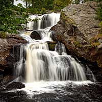 Photograph of multi tier waterfall in rocky, wooded area, Connecticut.