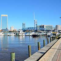 Photograph of Jacksonville, Florida harbor, boats, city skyline in background.