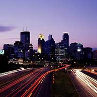 Photograph of Minneapolis, Minnesota skyline at night with light trails.