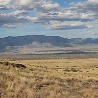 Photograph of prairie landscape with blue mountains, Albuquerque, New Mexico.
