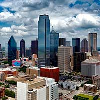 Photograph of Dallas, Texas cityscape with skyscrapers, clouds, blue sky.