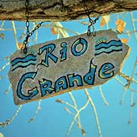 Photograph of painted sign reading Rio Grande hanging from branch.