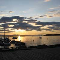 Photograph of sunset over a Vermont bay, clouds and sailboats.