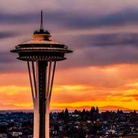Photograph of Space Needle in Seattle, Washington, against orange sunset.