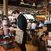 Photograph of a male barista preparing coffee in Seattle, Washington.