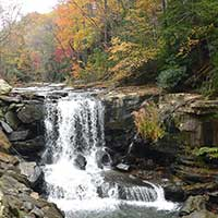 Photograph of small rocky appalachian waterfall in autumn wooded area.
