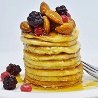 Photograph of a stack of pancakes with toppings.