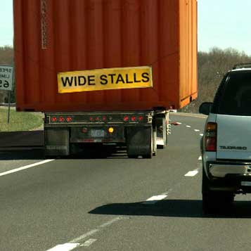 "Manipulated photograph showing large truck with ""wide stalls"" banner."