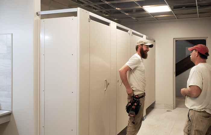 Photograph showing two installers standing near Hadrian Elite Plus toilet partitions.