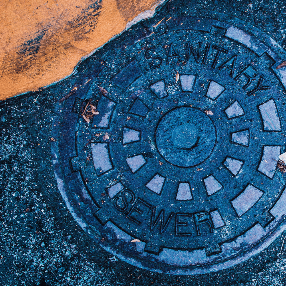 Photograph of a manhole cover for a blog post about wastewater testing.